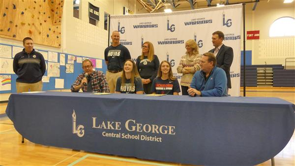 two student athletes and their parents and coaches sitting at a table