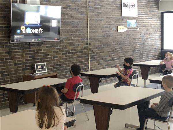 elementary students watching a virtual puppet show